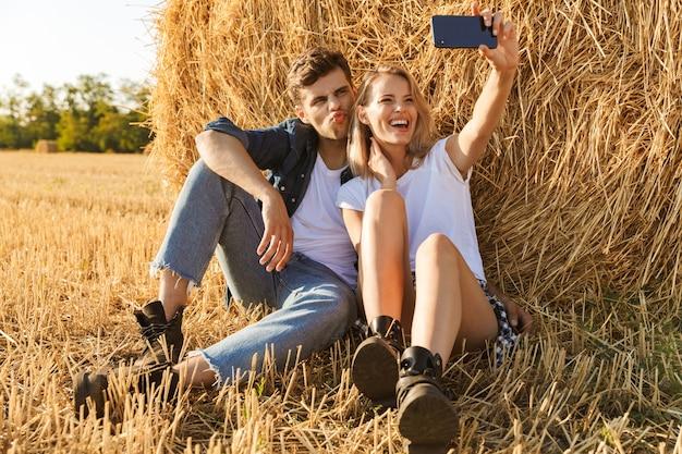 Foto van moderne paar man en vrouw selfie te nemen zittend onder grote hooiberg in gouden veld, tijdens zonnige dag
