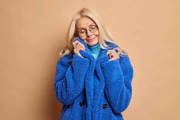 Foto van modieuze blonde vrouw kantelt hoofd en sluit ogen draagt ronde bril blauwe bontjas herinnert aan iets aangenaams.