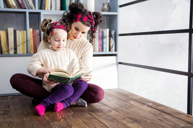 Foto van moeder en dochter zitten op de vloer en lezen