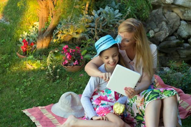 Foto van moeder met dochter buitenshuis op picknick, spelen met digitale tablet