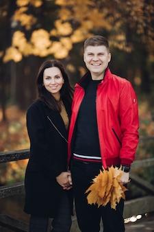 Foto van moeder met lang zwart haar in zwarte jas, mooie vader met kort donker haar in rood jasje met boeket herfstbladeren