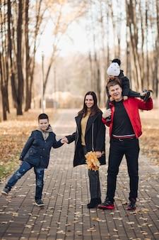 Foto van moeder met lang zwart haar in zwarte jas, vader met kort haar in rood jasje, mooie kleine jongen met haar jongere zus met boeketten van herfstbladeren