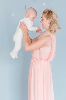 Foto van moeder speelt en werpt een kind in de kinderkamer tegen de achtergrond van de blauwe muur