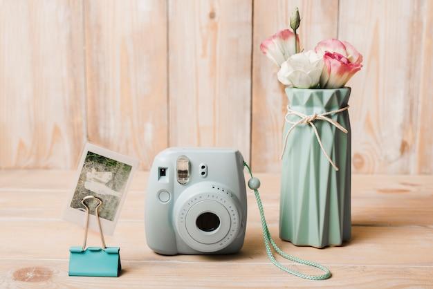 Foto van momentopname; mini-instantcamera; bulldog paperclip en bloemenvaas op houten tafel