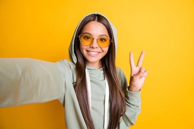 Foto van mooi donkerbruin haar kind toont arm vinger v-teken op selfie hoodie geïsoleerd op gele kleur achtergrond