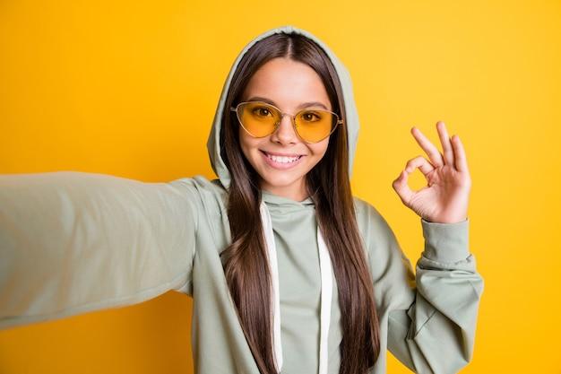 Foto van mooi gezicht brunette toont vinger okey symbool levensstijl stijlvolle hoodie geïsoleerd op gele kleur achtergrond