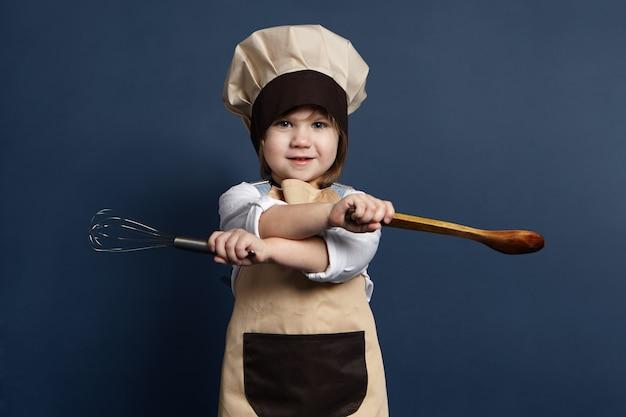 Foto van mooi klein meisje dat chef-kok glb en schort draagt die handmixer of draadklopper in één hand en houten lepel in andere hand houdt, gaat eieren kloppen of tomatensaus maken. eten en koken concept