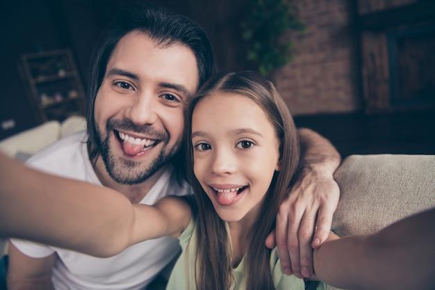 Foto van mooi klein schattig meisje en knappe jonge papa zitten op comfortabele bank