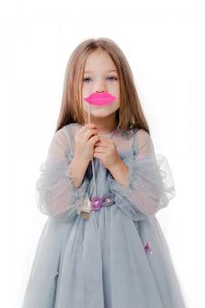 Foto van mooi meisje in een grijze jurk en met kartonnen lippen