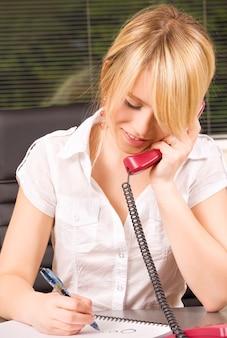 Foto van mooi meisje met telefoon in kantoor