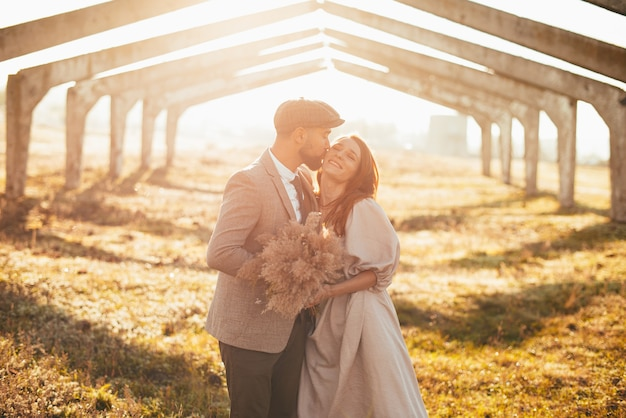 Foto van mooi paar, bruidegom kussen vrouw buiten bij zonsondergang