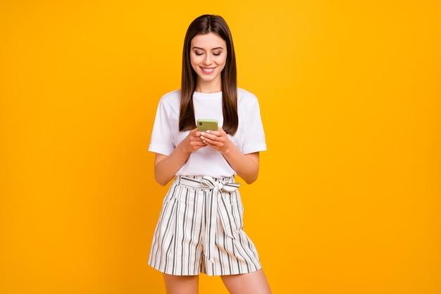 Foto van mooie aantrekkelijke dame telefoon handen houden lezen e-mail uitnodiging feest vrienden dragen casual wit t-shirt gestreepte zomer korte broek geïsoleerde levendige gele kleur muur