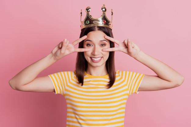 Foto van mooie aantrekkelijke dameshanden tonen twee v-tekens bedekken ogen echte glimlach draag kroon op roze achtergrond