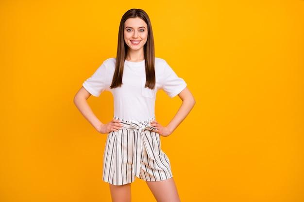 Foto van mooie aardige dame met armen naast elkaar staan zelfverzekerd goed humeur dragen casual wit t-shirt gestreepte zomer mini korte broek geïsoleerd levendige gele kleur muur