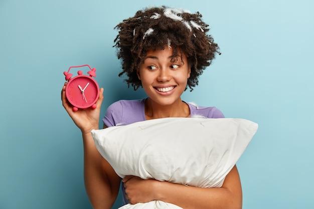 Foto van mooie afro-amerikaanse vrouw met krullend haar, toont tijd op wekker, blij om 's nachts lang te slapen, lacht positief, houdt zacht wit kussen vast, geïsoleerd over blauwe muur. slapen