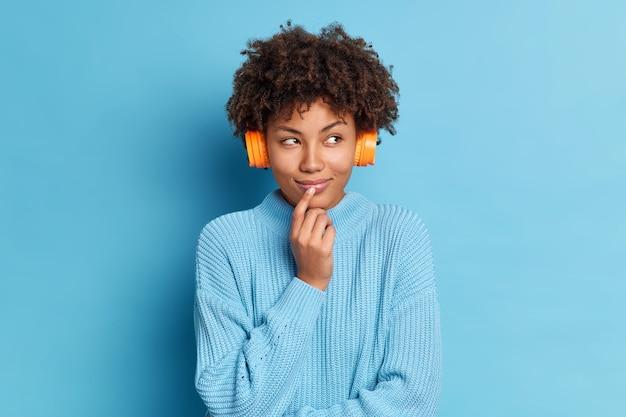 Foto van mooie afro-amerikaanse vrouw staat bedachtzaam indoor luistert aangenaam liedje dat haar goede herinneringen uit het verleden brengt draagt casual jumper koptelefoon op oren