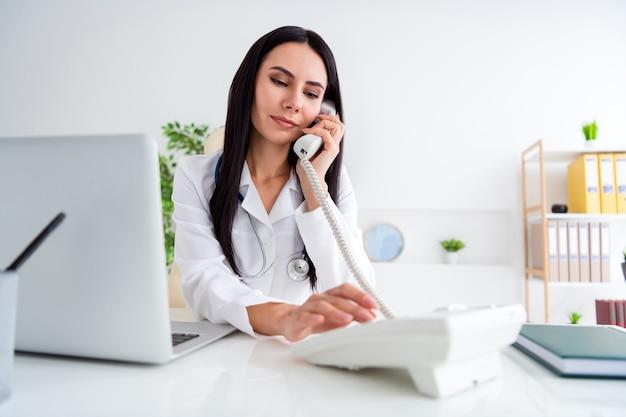 Foto van mooie arts serieuze dame gebruik netbook op tafel sprekende telefoon