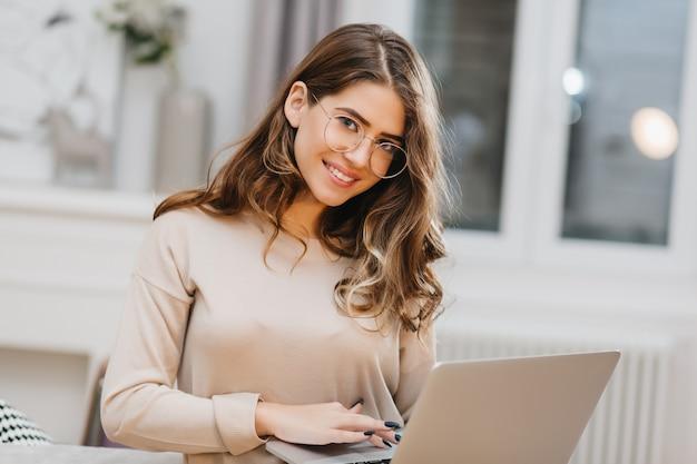 Foto van mooie blanke vrouw in glazen met behulp van computer met charmante glimlach
