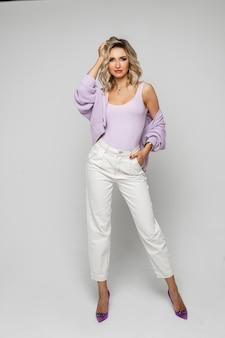 Foto van mooie blanke vrouw met golvend blond haar, zachte huid in paarse modieuze blouse en witte broek