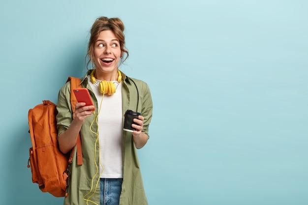 Foto van mooie blije duizendjarige meisje leest publicatie op moderne mobiele telefoon, geniet van muziekliedje van de applicatie, heeft een koptelefoon op de nek, draagt vrijetijdskleding, drinkt koffie om mee te nemen, draagt rugzak
