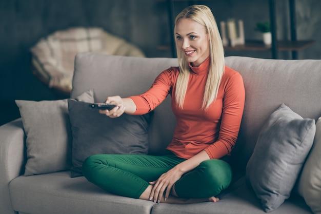 Foto van mooie blonde dame huiselijke stemming bedrijf tv afstandsbediening veranderende kanalen zoeken favoriete film zitten comfortabele bank casual outfit woonkamer binnenshuis