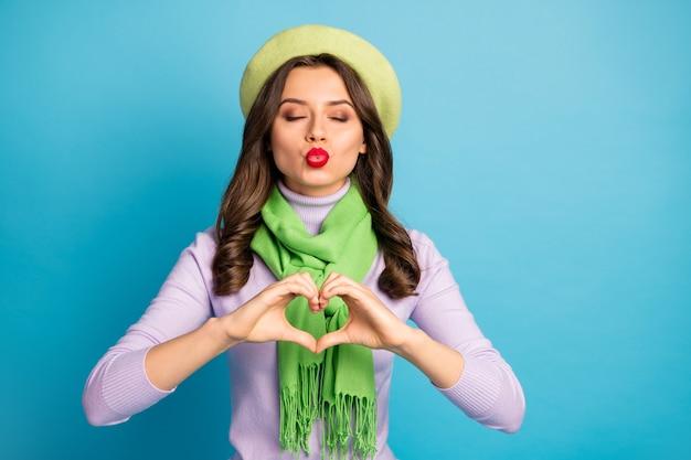 Foto van mooie charmante dame hand in hand in hart figuur lucht kussen vriendje tedere gevoelens dragen trendy groene baret paarse coltrui sjaal geïsoleerde blauwe kleur muur