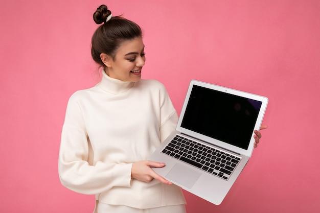 Foto van mooie charmante glimlachende vrouw met verzameld donkerbruin haar die de computer van de witte sweaterholding dragen