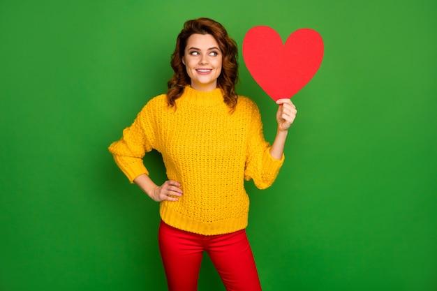 Foto van mooie charmante golvende dame houden papier hartvorm briefkaart romantiek datum uitnodiging denk aan antwoord dragen gele gebreide trui rode broek geïsoleerd helder groene kleur muur