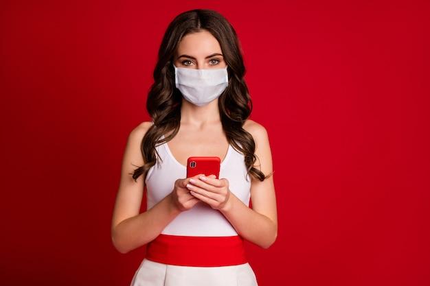 Foto van mooie charmante golvende dame millennial hold telefoon chatten vrienden lezen bericht typen antwoord covid nieuws draag medisch masker witte jurk geïsoleerde heldere rode kleur achtergrond