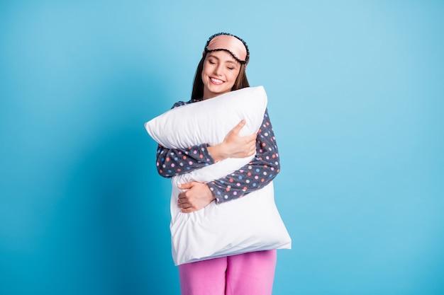 Foto van mooie charmante jonge meid liefde slaap gesloten ogen knuffel kussen glimlachen miss ontspannen na een lange werkdag draag masker gestippeld shirt pyjama nachtkleding geïsoleerde blauwe kleur achtergrond
