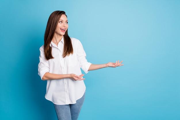 Foto van mooie dame die armen toont directe lege ruimte draag wit overhemd jeans geïsoleerde blauwe kleur achtergrond