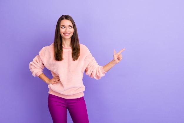 Foto van mooie dame die vinger op lege ruimte aangeeft kijkt kant op violette muur