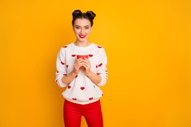 Foto van mooie dame die warme koffie drinken beker toothy glimlachen geniet van vrije tijd ontspanning draag harten patroon witte trui