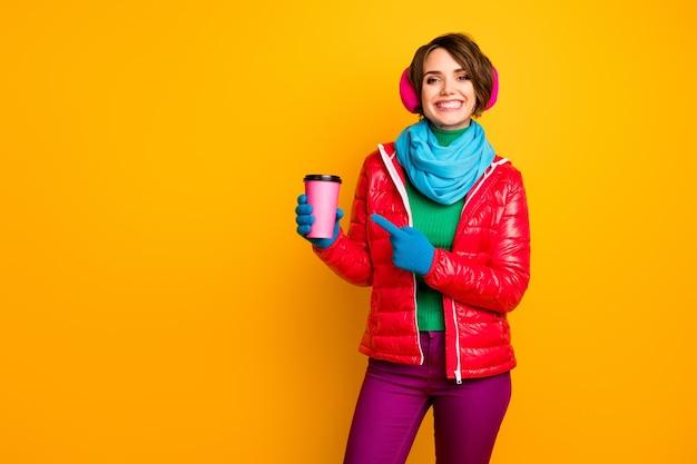 Foto van mooie dame houd papieren mok afhalen koffie regisseren vinger op roze beker verse americano dragen casual rode jas blauwe sjaal handschoenen oor covers broek
