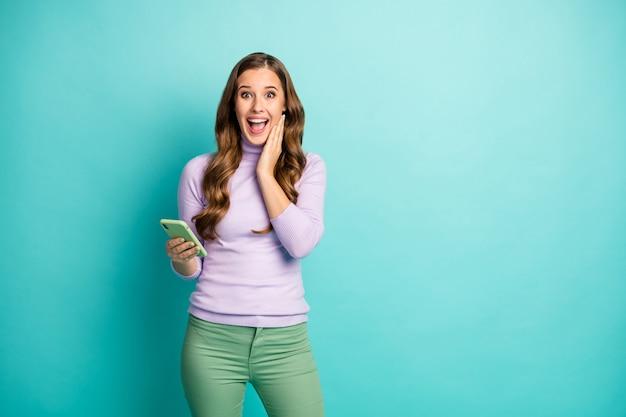 Foto van mooie dame houd telefoon lezen blogpost positieve opmerkingen open mond hand op wang dragen violet trui groene broek geïsoleerd pastel blauwgroen blauwe kleur