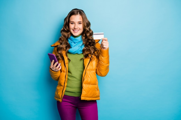 Foto van mooie dame houden telefoon online kopen met plastic creditcard betalen pass dragen gele overjas sjaal violet broek groene trui geïsoleerde blauwe kleur muur
