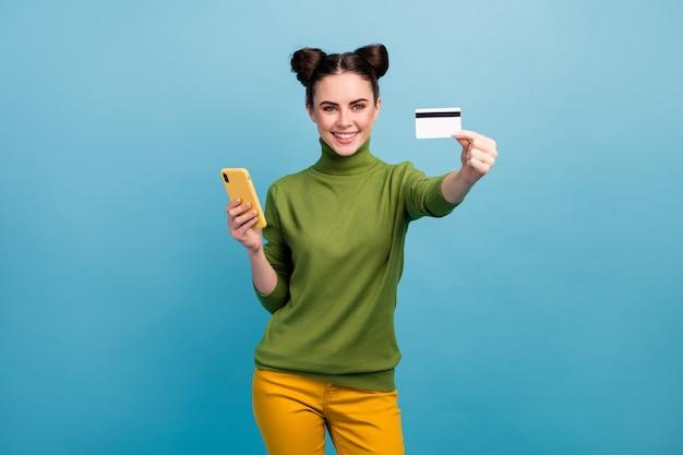 Foto van mooie dame houden telefoon show plastic creditcard adviseren cool service online betaling bank nieuwigheid slijtage groene coltrui gele broek geïsoleerde blauwe kleur muur