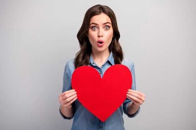 Foto van mooie dame houdt groot rood papier hart liefhebbers dag onverwachte creatieve uitnodiging vriendje open mond slijtage casual jeans denim overhemd geïsoleerde grijze kleur