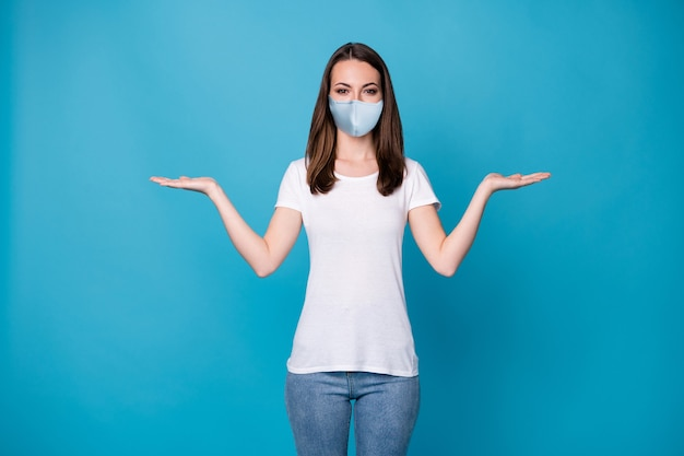 Foto van mooie dame houdt open palmen armen met geselecteerde pick covid nieuwigheid producten verkoop korting seizoen winkelen draag medisch masker wit t-shirt jeans geïsoleerde blauwe kleur achtergrond