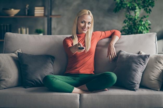 Foto van mooie dame huiselijke stemming houden tv afstandsbediening veranderende kanalen zoeken favoriete film zitten comfortabele bank casual outfit woonkamer binnenshuis