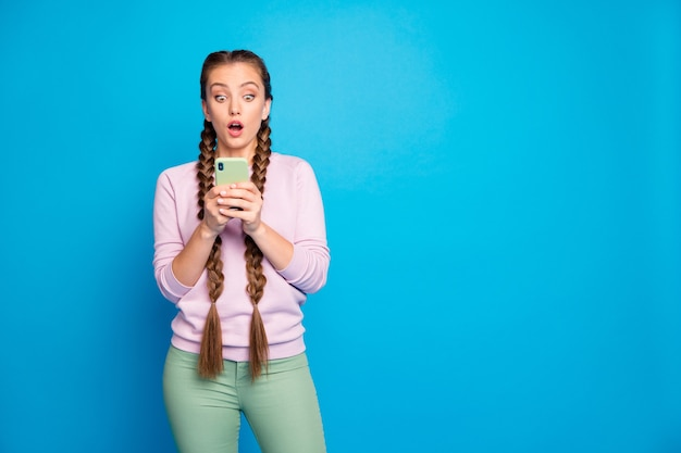 Foto van mooie dame lange vlechten met telefoonhanden lezen ongelooflijk slecht nieuws afkeer op post dragen casual pullover broek geïsoleerde blauwe kleur achtergrond