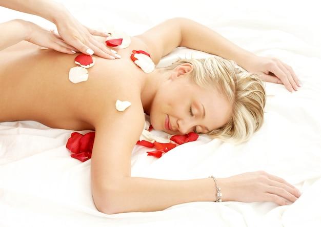Foto van mooie dame met bloemblaadjes in massagesalon