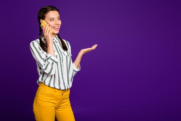 Foto van mooie dame met telefoon dichtbij oor sprekende vrienden opgewonden positieve stemming vakantie tijd draag gestreept shirt gele broek geïsoleerde paarse kleur achtergrond
