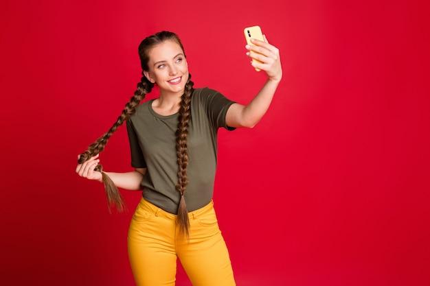 Foto van mooie dame met telefoon handen maken selfies skype spreken met vrienden tonen nieuw kapsel dragen casual gele broek groen t-shirt geïsoleerde rode kleur achtergrond