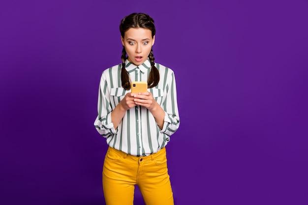 Foto van mooie dame met telefoon open mond lezen nepnieuws negatieve opmerkingen dragen gestreepte shirt gele broek geïsoleerde paarse kleur achtergrond
