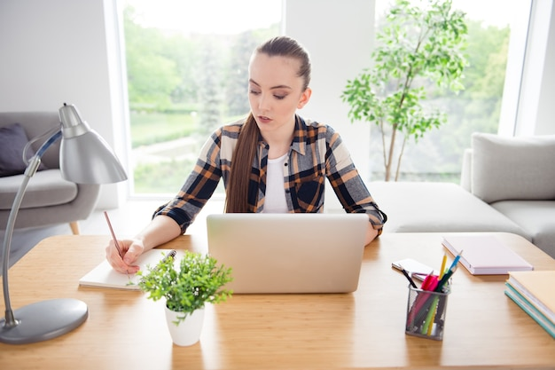 Foto van mooie dame student browsen notebook netbook onderwijs pass sessietaken binnenshuis