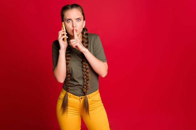 Foto van mooie dame telefoon vasthouden handen spreken met collega's vinger op lippen belangrijke discussie dragen casual gele broek groen t-shirt geïsoleerde rode kleur achtergrond