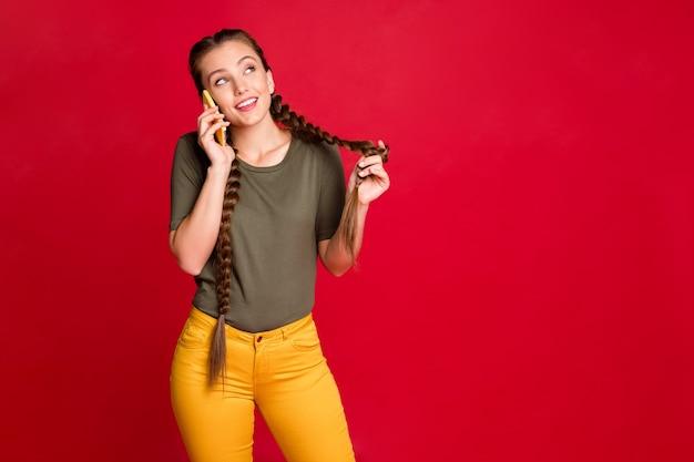Foto van mooie dame telefoon vasthouden handen spreken met vrienden bespreken vers nieuws roddels geruchten dragen casual gele broek groen t-shirt geïsoleerde rode kleur achtergrond