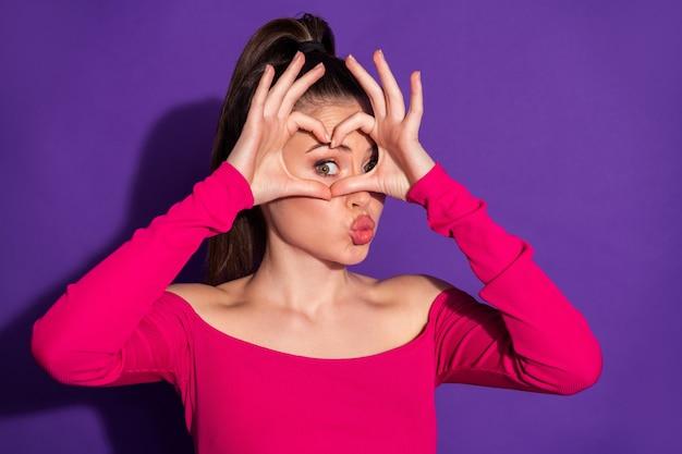 Foto van mooie dame vingers oog hart vorm lippen stuur lucht kus draag roze ongeklede schouders top geïsoleerde violette kleur achtergrond