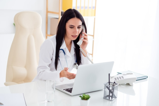 Foto van mooie dokter lady spreken telefoon raadpleging patiënt kijken scherm laptop